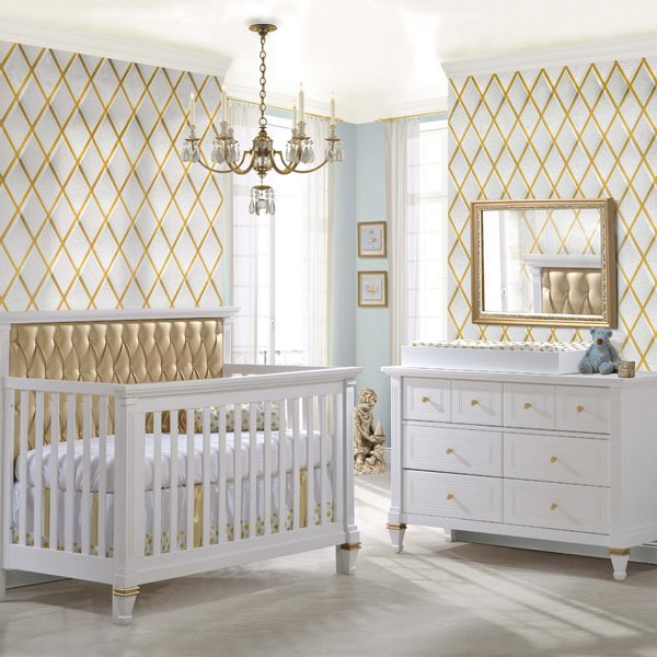 "White nursery with gold diamond patterned wallpaper, a gold mirror, a white double dresser with gold knobs and a white Belmont Gold ""5-in-1"" Convertible Crib with Gold Diamond Tufted Upholstered Headboard Panel"