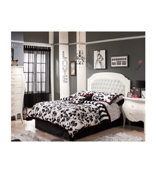 Dark walled bedroom with white nightstand, dresser and double bed with a white upholstered headboard panel with black and white sheets