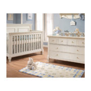 Baby nursery with blue walls and white crib and double dresser with blue and yellow starred area rug