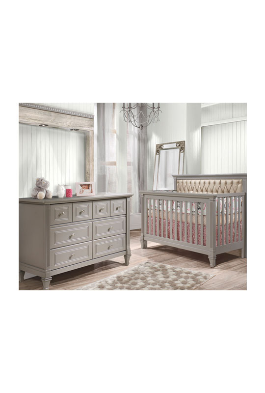 White wood panelled walls with darker floors and grey double dresser and crib with pink sheets and a platinum diamond tufted upholstered panel