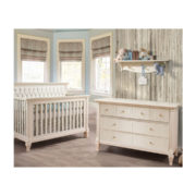 Blue and grey bedroom with wood panelled wall and white crib and double dresser