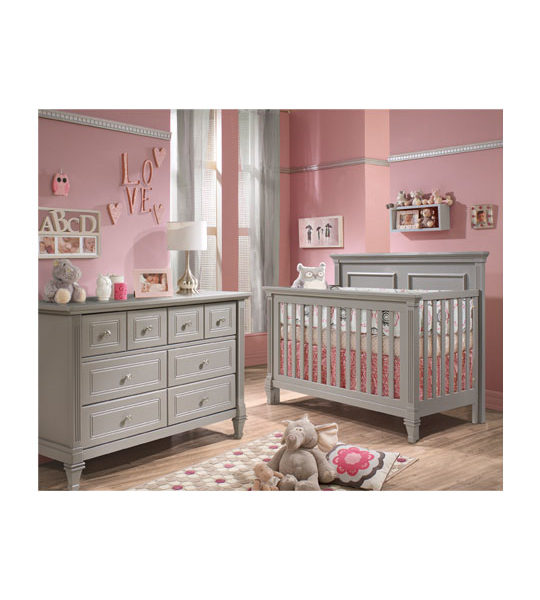 Pink painted walls in a girl's nursery with grey crib with pink sheets and double dresser