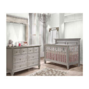 White wood panelled walls with darker floors and grey double dresser and crib with pink sheets