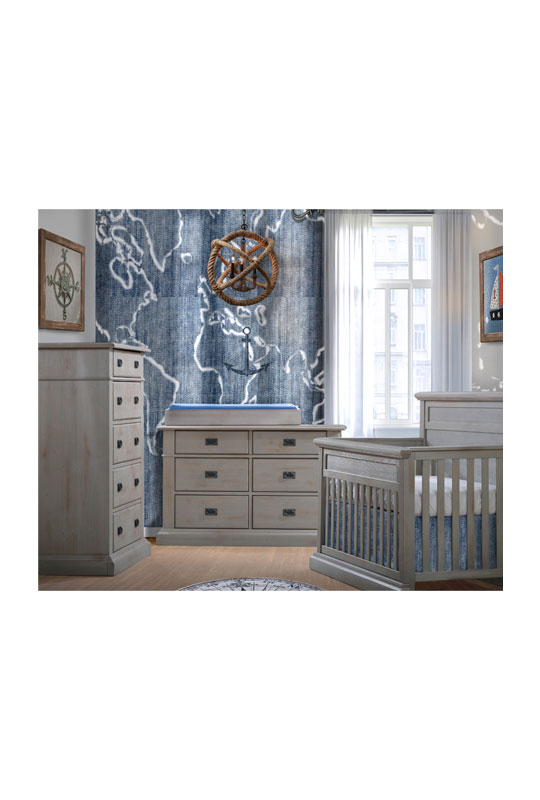 Baby room with blue naval wall and decor, with grey chalet crib, double dresser and 5 drawer dresser with black metallic handles