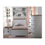 Bedroom with wood panelled walls, pink curtain and sheets with white wooden twin bed, two drawer nightstand, and 5 drawer dresser with black metallic handles with cognac tops