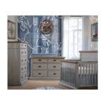 Baby room with blue naval wall and decor, with grey chalet crib, double dresser and 5 drawer dresser with black metallic handles with cognac tops