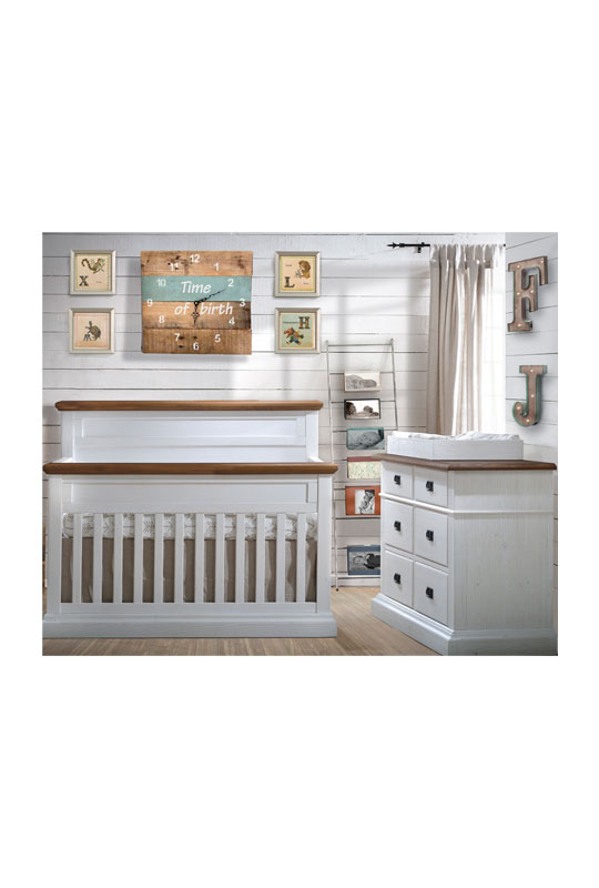 White Bedroom with wood panelled walls, white classic wooden crib and double dresser with cognac topswith a white wooden changing tray