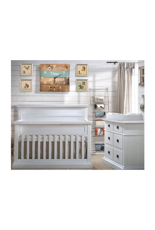 White Bedroom with wood panelled walls, white classic wooden crib and double dresser with a white wooden changing tray