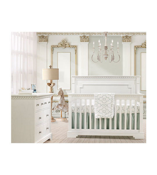 White and gold baby room with white classic double dresser and crib with detailed moldings