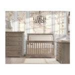 Baby room with world map wallpaper, wooden crib with beige upholstered panel, 3 drawer dresser and 5 drawer dresser