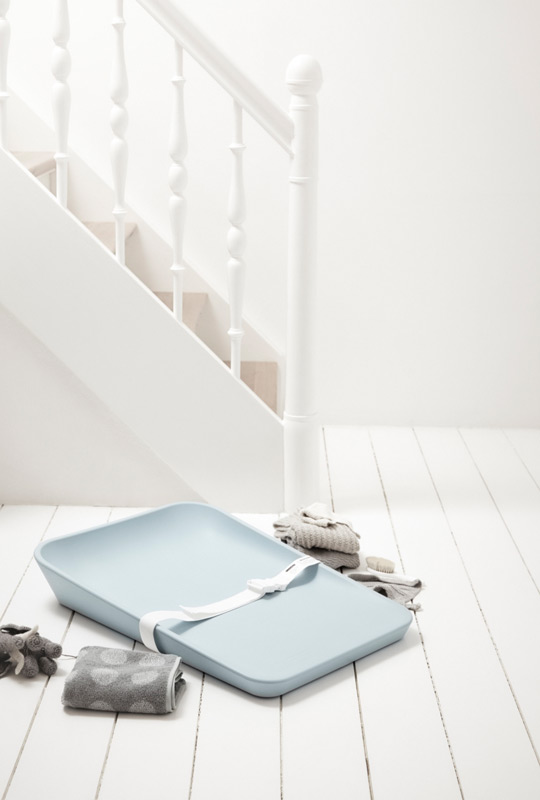 Matty Sleek portable changing mat in a light blue on a white wooden floor with staircase and grey folded towels