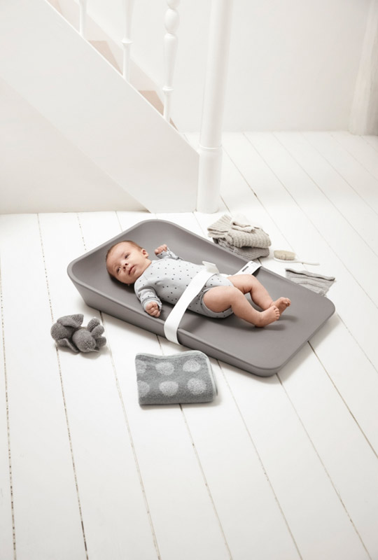 Baby strapped in and laying on grey changing mat on a white floor with grey towel, toy and clothes