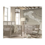 Rustic baby nursery with a map of italy wallpaper and grey wooden double dresser and crib with beige upholstered panel and a rocking chair with beige cushions