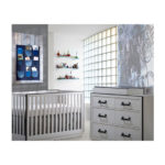 White and grey baby room with a white crib and white wooden double dresser with black metallic handles