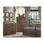 Baby nursery with grey floors, brick walls, dark brown wood crib, double dresser, 5 drawer dresser with black handles
