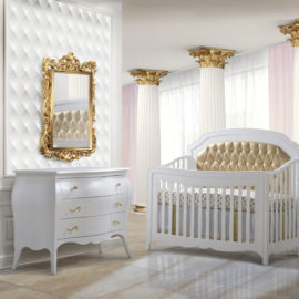 White Regal baby nursery with white columns with gold edges, a gold wall mirror, white 3 drawer dresser and white crib with gold diamond tufted upholstered panel