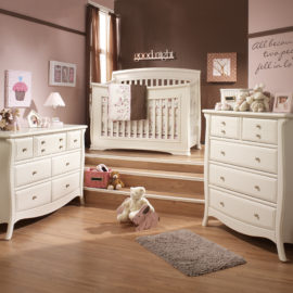 Pink and brown baby nursery with white double dresser and 5 drawer dresser with steps leading up to a white crib