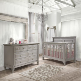 Baby room with white wood panelled walls, grey crib and a double dresser