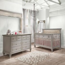 Baby room with white wood panelled walls, grey crib with a diamond tufted upholstered panel in platinum and a double dresser