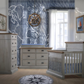 Baby room with blue naval wall and decor, with grey chalet crib, double dresser and 5 drawer dresser with black metallic handles and with cognac tops