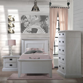 Bedroom with wood panelled walls, pink curtain and sheets with white wooden twin bed, two drawer nightstand, and 5 drawer dresser with black metallic handles