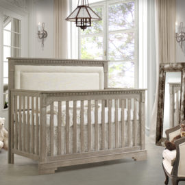 Baby room with grey convertible crib in sugar cane with a beige upholstered panel, rustic mirror