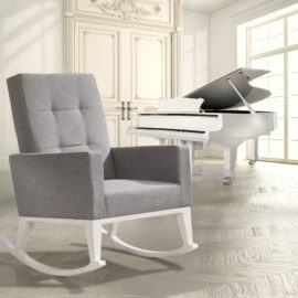 Rocking chair with white legs and grey seat with a white grand piano in a big white room