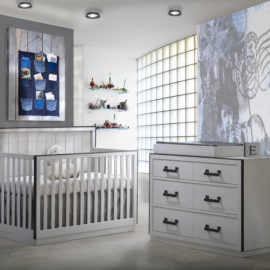 Grey bedroom with white wooden crib and double dresser and a white changing tray with blue decoratiosn
