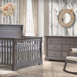 Baby Nursery in beige with a white bark wallpaper and featuring a wooden convertible Crib & Double Dresser in grigio