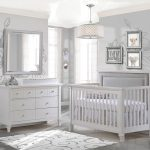 Grey nursery with flower wallpapers featuring a white crib with a grey upholstered headboard panel in grey, a white double dresser and white changing tray