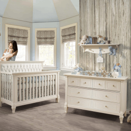 Beige and blue nursery with a wooden panelled wall, white dresser and crib with a white diamond tufted upholstered panel, blue decorations, with mom holding and cradling baby