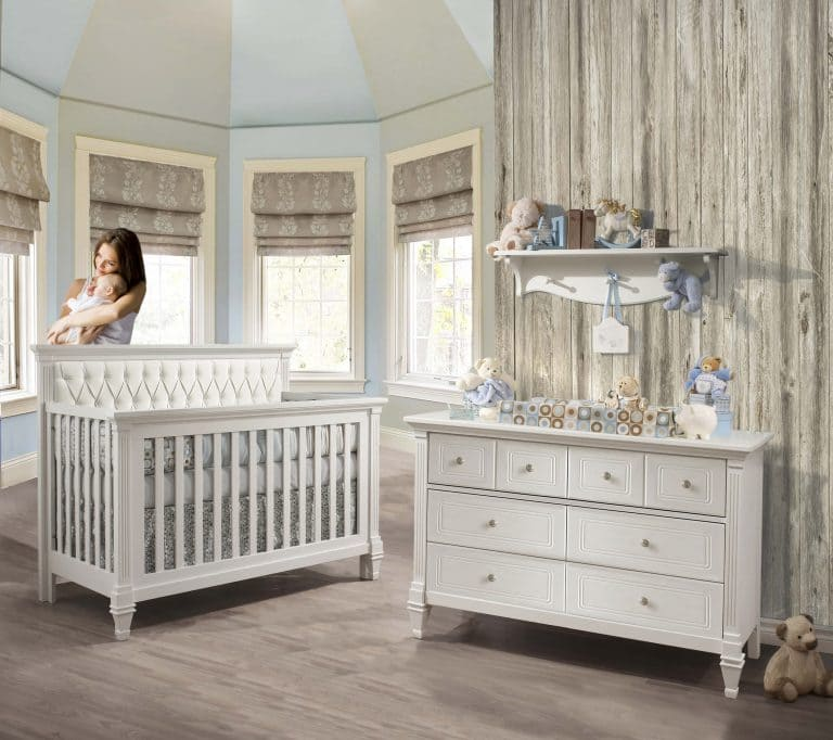 Blue and grey baby nursery with a wooden panelled wall, a double dresser and a crib with a white diamond tufted upholstered panel with mom holding baby