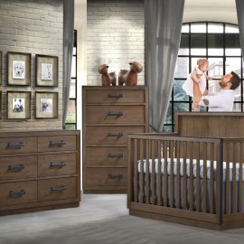 Baby nursery with white brick walls, cognac colored wooden crib, double dresser and 5 drawer dresser with dad holding up baby girl