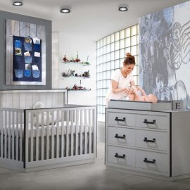 Grey nursery with white chalet wooden crib, double dresser and changing tray, with mom changing baby