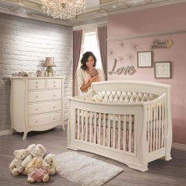 Classic Baby Room with pink wall and white brick wall, featuring a crib and dresser in Linen color with a mom holding baby