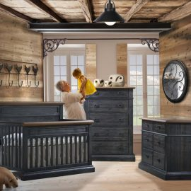 Rustic Baby Room with wooden walls and ceiling, featuring a crib, double dresser and 5 drawer dresser in black chalet & cognac tops with a grandma holding up baby girl in yellow dress