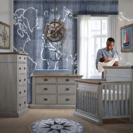 Baby room withe blue wallpaper and naval decoration with crib, double dresser and 5 drawer dresser in grey chalet & cognac tops, with a dad holding baby