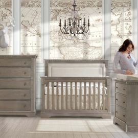 Beige and white baby room with a wooden crib with a beige upholstered panel, and dressers Ithaca Collection with a pregnant mom holding belly