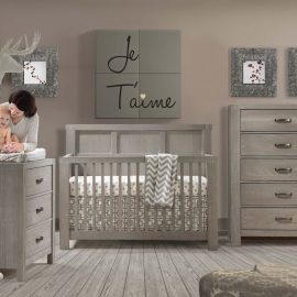 Grey Baby Room with wooden crib, 5 drawer dresser and a mom holding baby