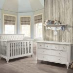 Blue and grey baby nursery with a wooden panelled wall, a double dresser and a crib with a white diamond tufted upholstered panel
