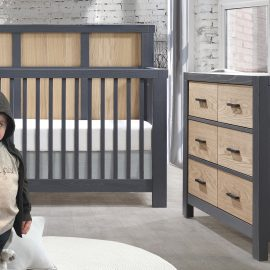 White and blush pink nursery with graphite crib and double dresser with natural oak panels