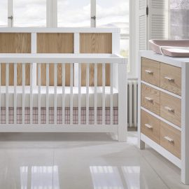 White and blush pink nursery with white crib and double dresser with natural oak panels