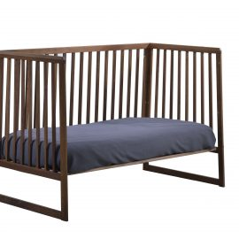 Dark brown wooden crib used as a daybed