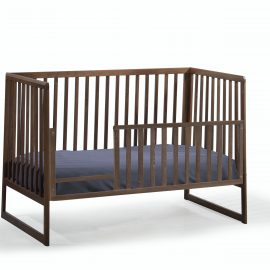 Dark brown wooden crib used as a toddler bed with gate