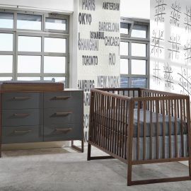 Baby room with dark wooden crib and changing table with glossy grey facades