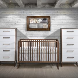 Nursery with white brick walls and dark brown wood crib and dressers with white facades