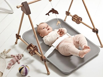 Baby laying on grey changing mat on the floor with safety belt attached playing with mobile