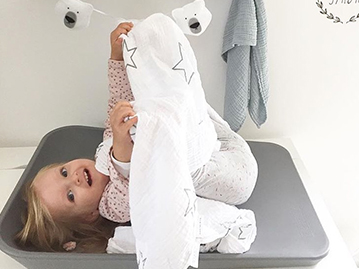 toddler girl laying on her back on a grey changing mat