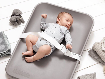 Baby laying on grey changing mat on the floor with safety belt attached